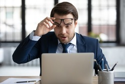 Surprised lucky 30s male ceo manager employee in formal wear can't believe his eyes, looking at laptop screen, feeling excited by unexpected news, salary increase notification or job promotion.