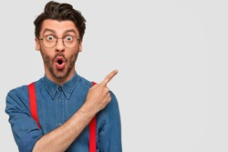 Surprised male hipster, keeps mouth opened, being stupefied as advertises something, wears fashionable shirt and red suspenders, indicates with fore finger at upper right corner. Omg concept