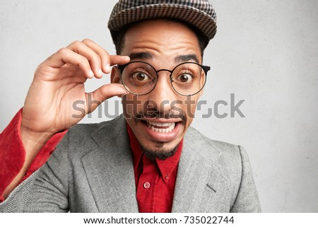 e0ffe863ecdf Surprised male nerd wears round spectacles, keeps hand on frame, wears cap  and jacket