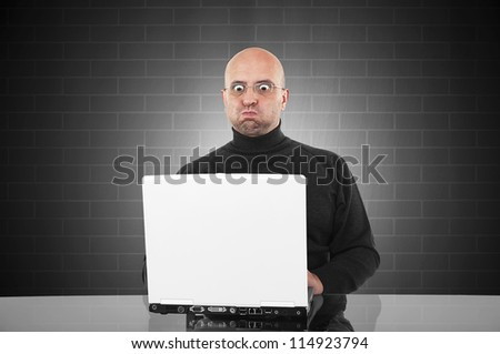 Surprised man blowing his cheeks and looking surprised to the monitor of his laptop