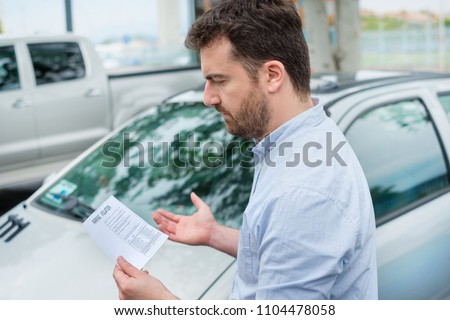 Surprised man finding parking ticket fine on his car Photo stock ©