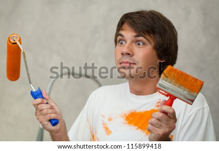 Surprised man holding paintbrushes and showing confuse
