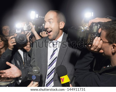 Surprised man in suit surrounded by paparazzi