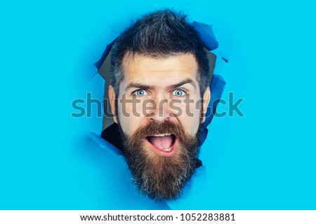 Surprised man looking through hole in blue paper. Bearded man making hole in paper. Man gazing seriously from hole in wall. Hole in paper with surprised man looking through. Copy space for advertise.