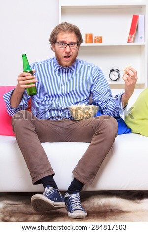 Surprised man ot the sofa with popcorn and beer