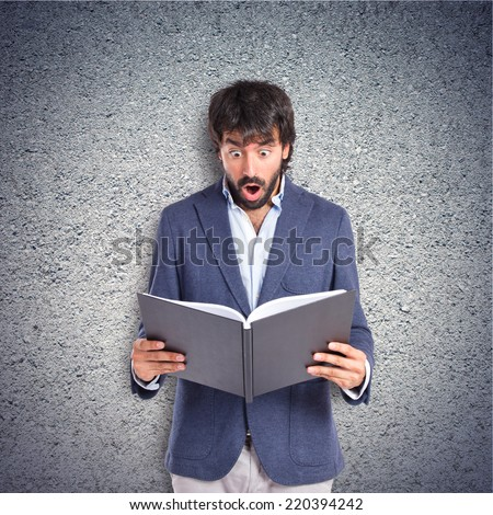 Surprised man reading a book over textured background