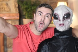 Surprised man taking a selfie with an alien