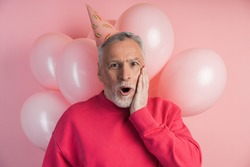 Surprised man with festive hat on his head smiling on pink background with balloons. Man isolated on pink background.