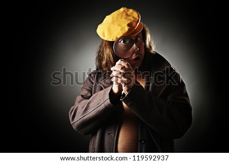 Surprised man with long hair and yellow cap looking through magnifying glass.
