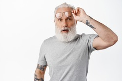 Surprised mature guy with long beard, take-off glasses and look in awe, staring at something amazing, standing in grey t-shirt against white background