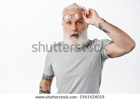 Surprised mature guy with long beard, take-off glasses and look in awe, staring at something amazing, standing in grey t-shirt against white background Сток-фото ©