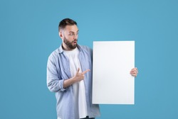 Surprised millennial man pointing at white blank poster on blue studio background, mockup for your ad design. Handsome Caucasian guy demonstrating empty banner with copy space