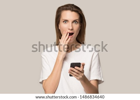 Surprised millennial woman isolated on grey studio background hold smartphone look at camera feel stunned by shocking unbelievable news, shocked female using cellphone get pleasant unexpected message