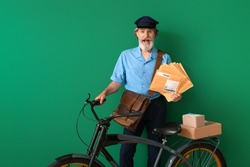 Surprised old postman with bicycle on color background