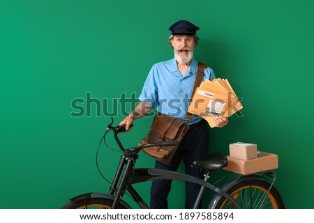 Surprised old postman with bicycle on color background Stockfoto ©