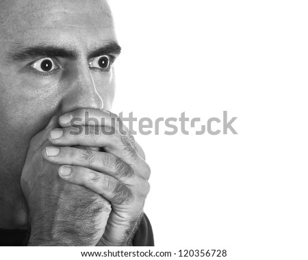 Surprised or scared young man covering his mouth with his hands.