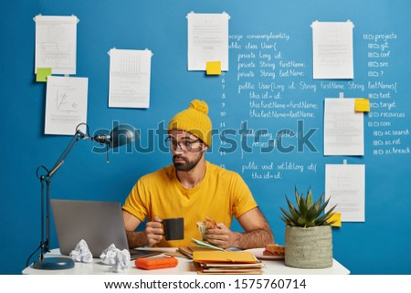 Surprised professional male IT professional freelancer focused in monitor of laptop, tries to improve code of application, drinks coffee and eats sandwich. Skilled geek develops application software