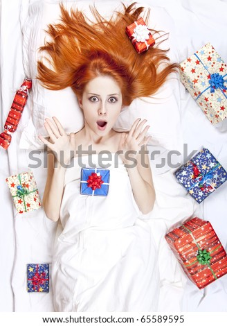 Surprised red-haired girl in bed with Christmas gifts. Studio shot.