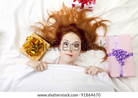 Surprised red-haired girl in bed with gifts. Studio shot.