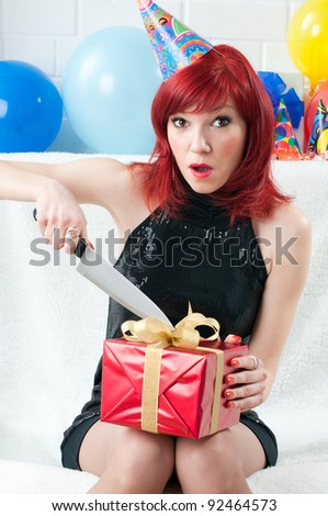 Surprised redheaded party woman opening a gift box with a kitchen knife