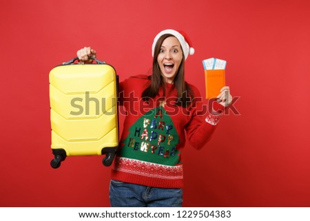 Surprised Santa girl keeping mouth wide open, hold yellow suitcase, passport boarding pass ticket isolated on red background. Happy New Year 2019 celebration holiday party concept. Mock up copy space