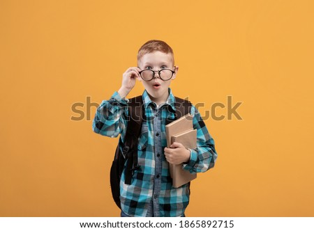 Surprised schooler with eyeglasses holding book on yellow studio background. Redhead schoolboy with backpack holding books, having amazed face expression, copy space. Books reading, education concept Stock photo ©