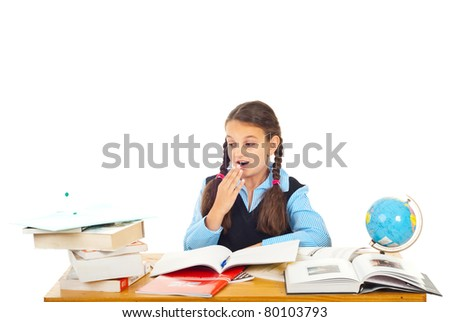 Surprised schoolgirl looking to books stack and sitting at pupil  isolated on white background