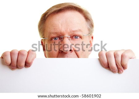 Surprised senior businessman peeking behind a white border