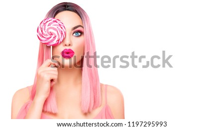Surprised sexy girl eating lollipop. Beauty Glamour Model woman with trendy pink hair style and beautiful makeup holding pink sweet colorful lollipop candy, isolated on white background. Sweets
