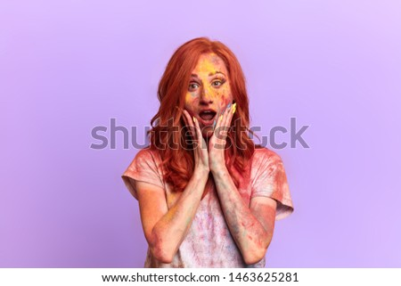 surprised shocked ginger woman with wide open mouth looking at the camera. close up portrait. woman with painted colourful face has heard shocking news. fear and fobia
