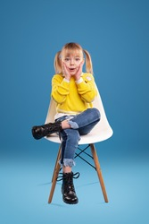 Surprised small girl in bright yellow sweater and jeans and black boots looking at camera and touching cheeks, while sitting alone on white chair against blue background in studio