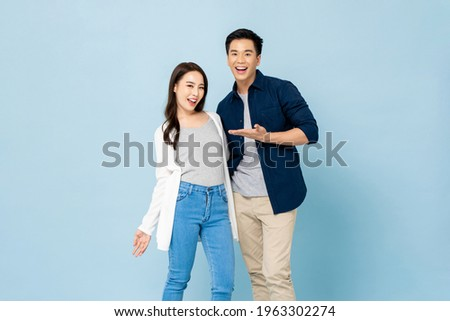 Surprised smiling Asian couple in casual clothes standing in light blue isolated studio background