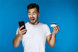 surprised smiling attractive guy is watching on the cell phone screen and holding credit card in the hand