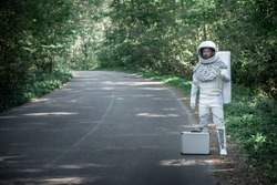 Surprised spaceman wearing full armor is standing near road in forest and looking at camera with smile. Full length portrait. Copy space on left side
