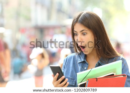 Surprised student girl watching smart phone content in the street