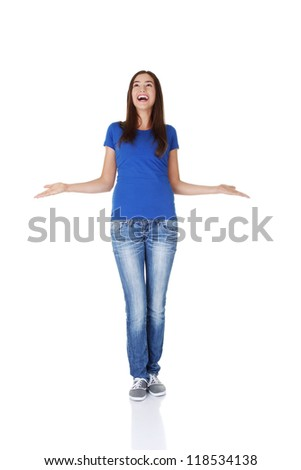 Surprised teen girl with outstretched arms looking up on copy space. Isolated on white.