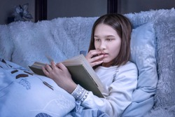 Surprised teenage girl reads an exciting book lays on bed in a cozy bedroom interior. Female college student holding novel and covering mouth with hand. Scary, mystery, suspense tale concepts.