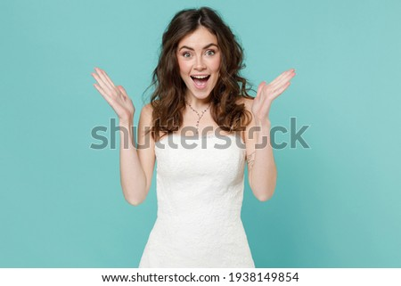 Surprised tender bride young woman 20s in beautiful white wedding dress spreading hands keeping mouth open isolated on blue turquoise background studio portrait. Ceremony celebration party concept