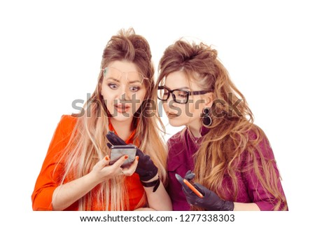 Surprised. Two shocked women young girls looking at mobile phone seeing shocking news message or photos with amazed emotion on face isolated on white wall background. Human emotion reaction expression