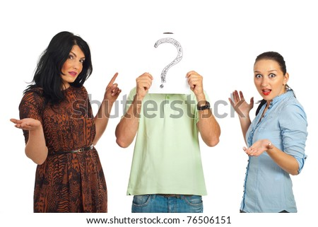 Surprised two women pointing to unknown guy who hold a question mark in front of his face isolated on white background