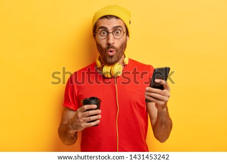 Surprised unshaven guy listens music in headphones, sends text messages on cell phone, types answer, drinks aromatic coffee from paper cup, watches surprising video in internet, wears stylish clothing #1431453242