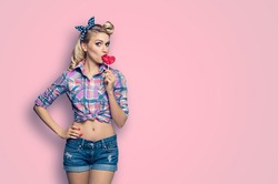 Surprised woman eating heart shape lollipop. Lovely girl in pin up. Blond model at retro fashion and vintage concept. Pink color studio background. Copy space for some ad slogan or text.