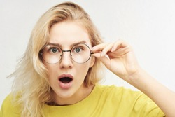 Surprised woman in round glasses with open mouth and bulging eyes looks into camera and sees something incredible and amazing isolated on white background