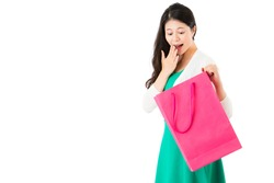surprised woman looking pink shopping bag on the white wall background over empty  area finding excited thing in the sack on copyspace.