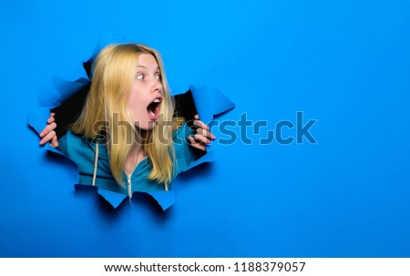 Surprised woman looking through hole in paper wall. Shocked girl making hole in paper. Pretty woman looks through hole. Blonde girl looks through ripped paper. Sale, discount, season sales. Copy space