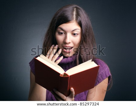 Surprised woman reading a book.