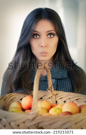 Surprised woman with a basket of ripe apples - Portrait of a surprised woman holding a basket full of organic apples