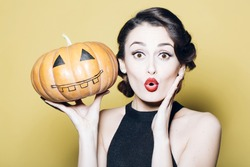 Surprised woman with beautiful face and retro hairdo and red lips holding pumpkin in studio on yellow background. Halloween concept