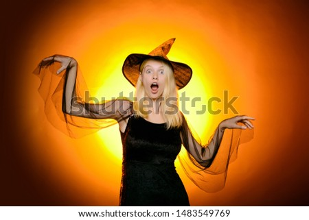 Surprised woman with beautiful face and retro hairdo and red lips holding pumpkin in studio on orange background. Holidays, decoration and party concept. Halloween decor. Toned image. Copy space