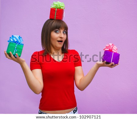surprised woman with open mouth holds a box with gifts on his head on a lavender background